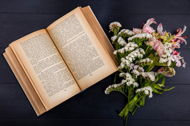 Top view of light pink flowers with an open book on a black surface
