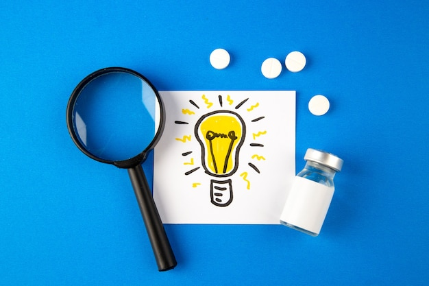 Top view lightbulb drawing with magnifier and pills on blue background hospital health virus covid- pandemic lab drug science
