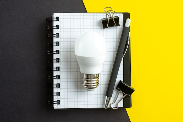 Top view of lightbulb spiral notebook on book and pens on black yellow background with free space