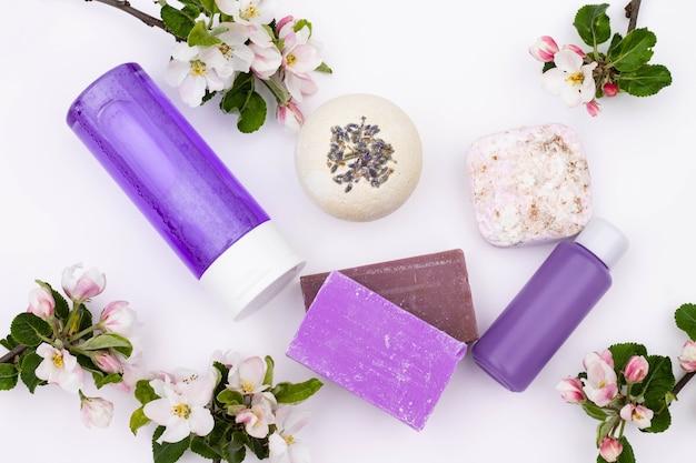 평면도. 라일락 화장품 병, 목욕 폭탄, 수제 비누, 흰색 배경에 배 꽃이 있는 목욕 소금. 천연 유기농 화장품 개념입니다. 플랫 레이