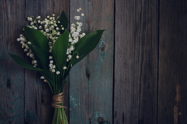 Top view lily of the valley on old wooden background