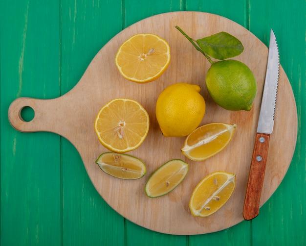 緑の背景のまな板にレモンとナイフでトップビューライムスライス
