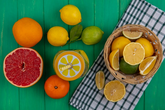 Top view lime slices with lemons in a basket on a checkered towel with oranges and half a grapefruit on a green background