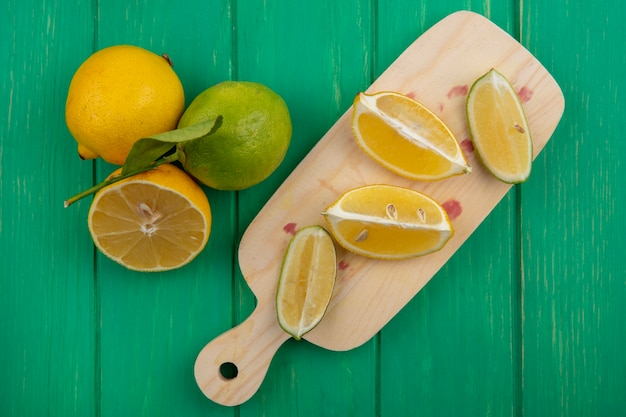 Вид сверху ломтики лайма с лимонами на разделочной доске на зеленом фоне
