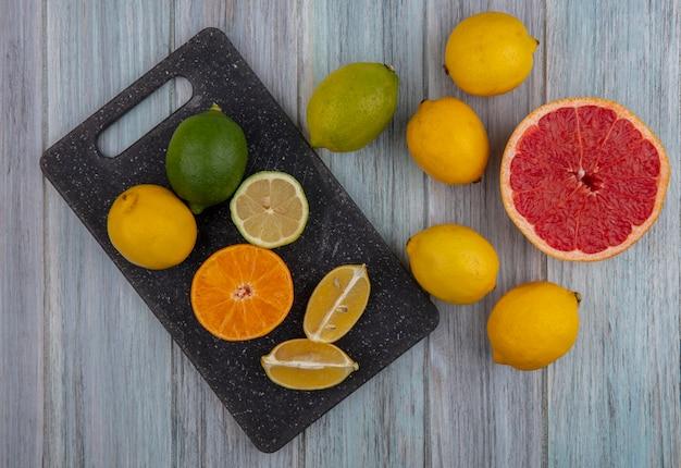 灰色の背景のまな板に半分オレンジグレープフルーツとレモンとトップビューライムウェッジ
