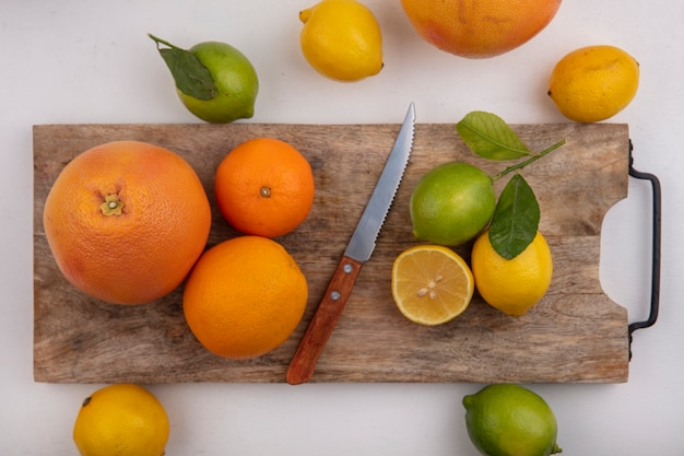 Vista dall'alto calce con limoni arance e pompelmo su una tavola con un coltello su uno sfondo bianco