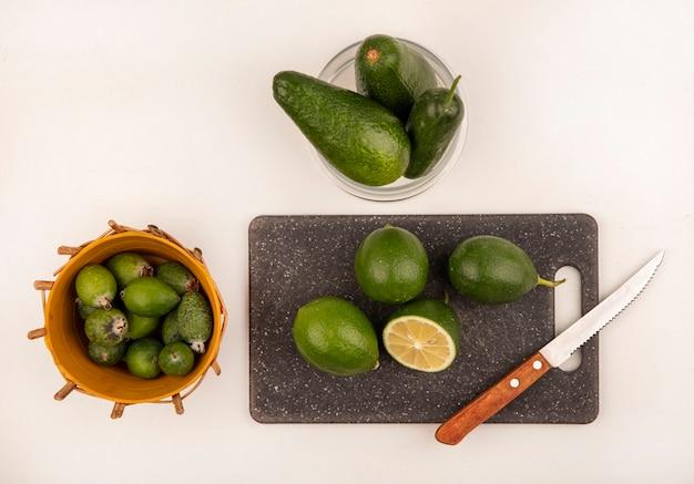Vista dall'alto di lime su una tavola da cucina con coltello con avocado e cetriolo su una ciotola di vetro con feijoas su un secchio su un muro bianco