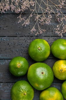 Top view limes on table big limes next to branches on the right side of table