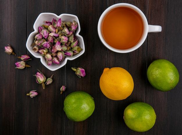 Vista dall'alto di lime con limone e una tazza di tè con germogli secchi su una superficie di legno