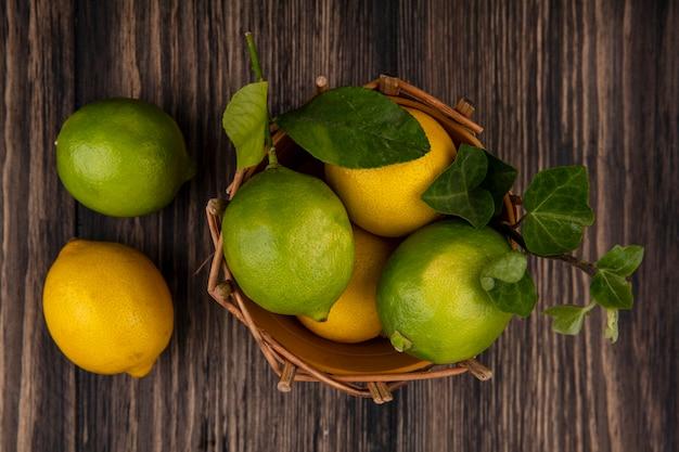 木製の背景のバスケットにレモンとトップビューライム