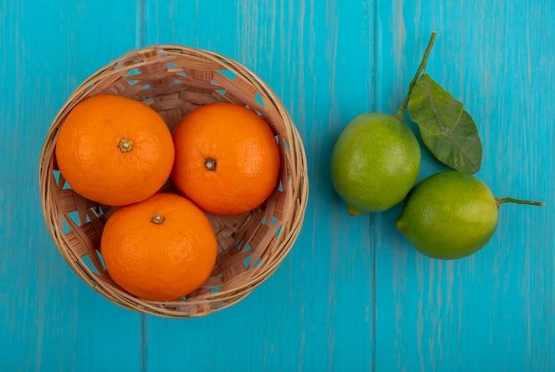 ターコイズブルーの背景のバスケットにオレンジとトップビューライム 無料写真