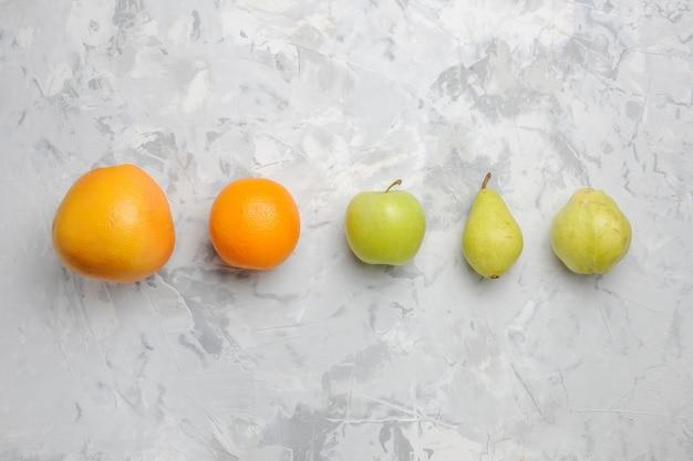 Вид сверху выложены свежими фруктами, грушами и мандаринами на белом фоне