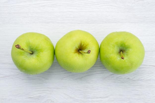 トップビューホワイトバックグラウンドフルーツまろやかなジュースの写真に緑のリンゴが並ぶ