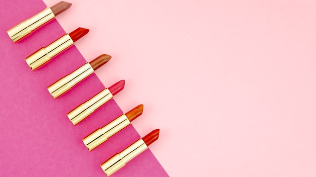 Top view lipsticks on colorful background with copy space