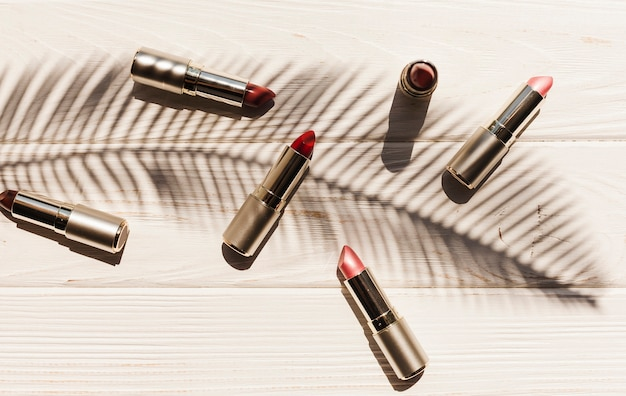 Top view lipsticks with palm branch shadow