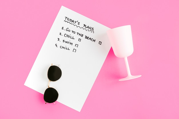 Top view list with cup and sunglasses