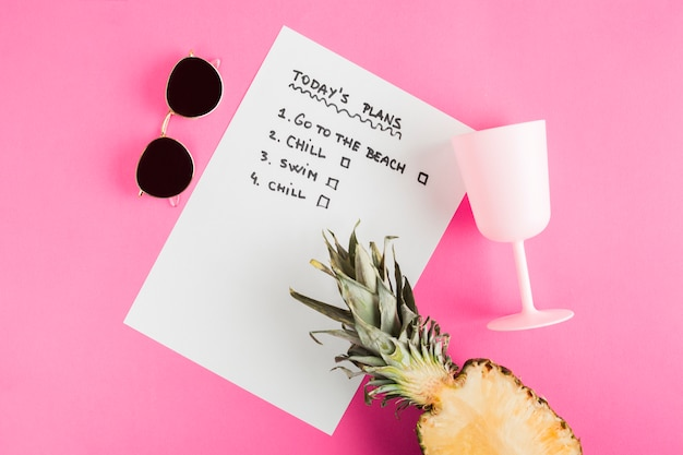 Top view list with pineapple, cup and sunglasses
