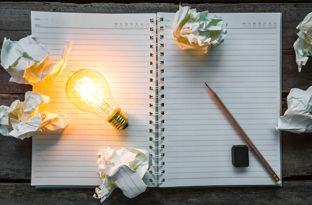Top view of lit light bulb on a notebook