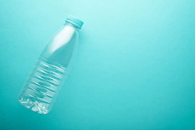 Top view liter plastic bottle with blue lid on turquoise, neo mint background with copy space