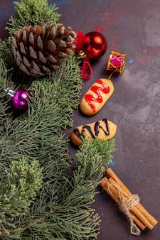 Vista dall'alto di biscottini con albero e coni sul tavolo nero