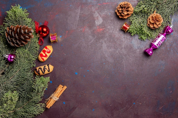 Top view of little biscuits with tree and cones on dark