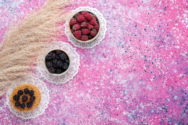 Top view of little blackberry cake with raspberries and fresh blackberries on the light pink surface