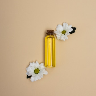 Top view little bottle of oil with flowers