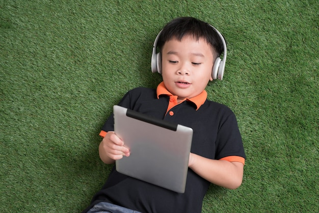 Top view of little boy in headphones using a digital tablet and smiling while lying on green grass