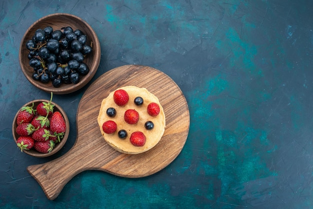 上面図紺色の表面に新鮮なイチゴで形成された丸く焼き上げられた小さなケーキ
