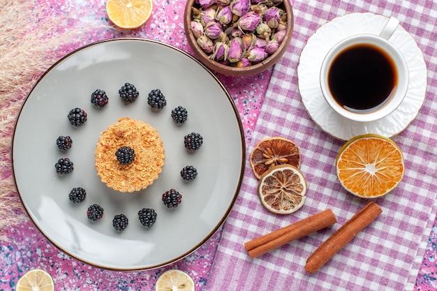 Vista dall'alto della piccola torta con frutti di bosco e tazza di tè sulla superficie rosa