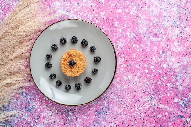 Vista dall'alto della piccola torta con frutti di bosco sulla superficie rosa