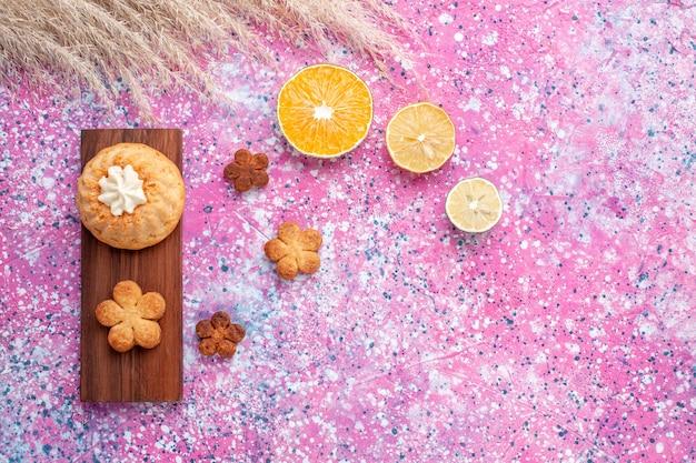 Vista dall'alto della piccola torta con biscotti e fette d'arancia sulla superficie rosa