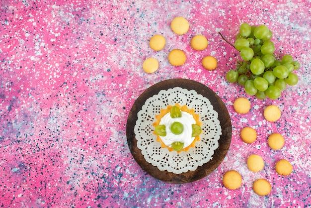 Vista dall'alto piccola torta con crema e insieme a uva verde sulla frutta torta superficie luminosa