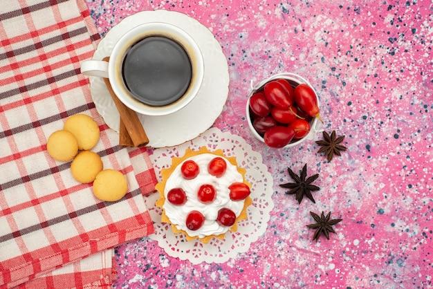 トップビューの色付きの表面色のコーヒーと一緒にクリームと新鮮なフルーツの小さなケーキ
