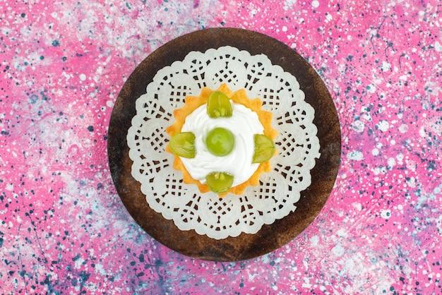 トップビューの明るい表面の果物の甘いクリームと緑のブドウの小さなケーキ
