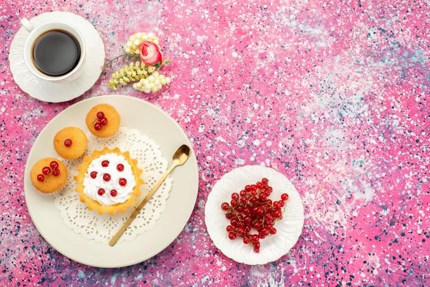 トップビューの明るい表面のクッキーティーにコーヒーカップと一緒にクリームクッキーの新鮮なクランベリーと小さなケーキ