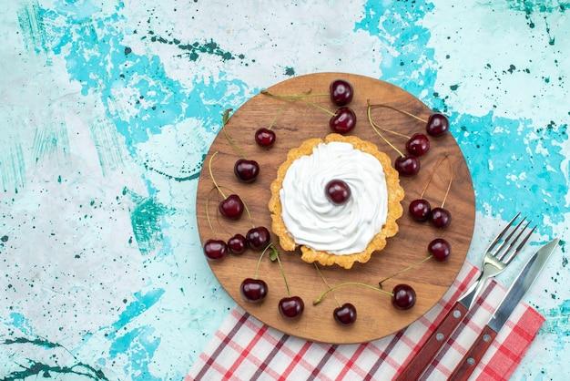 Vista dall'alto della piccola torta con crema e ciliegie fresche su azzurro, dolce di biscotto torta di frutta fresca