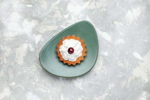 Vista dall'alto della piccola torta con crema all'interno del piatto sulla luce, dolce crema per torta