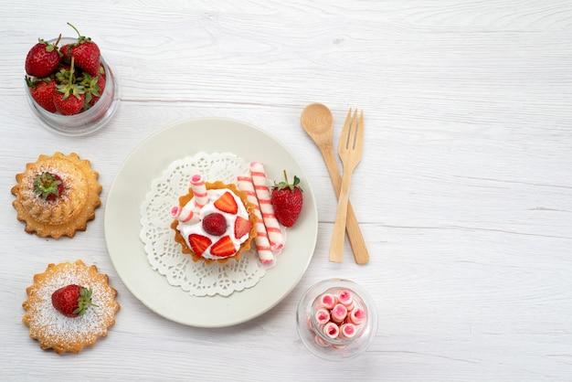 Vista dall'alto della piccola torta con crema e fragole a fette torte caramelle su bianco, zucchero dolce torta di frutta