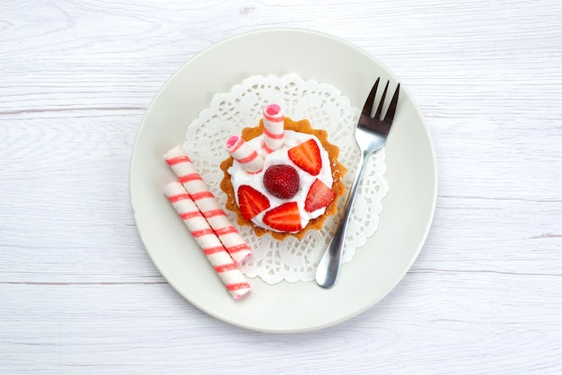 Top view of little cake with cream and sliced strawberries inside plate on white, fruit cake berry sweet sugar