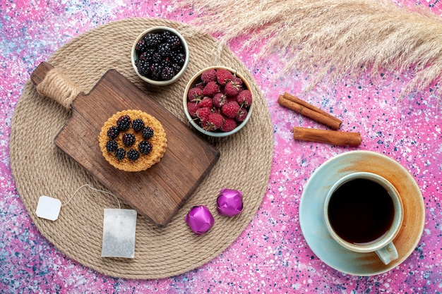 Top view of little cake with different berries and cup of tea on pink surface