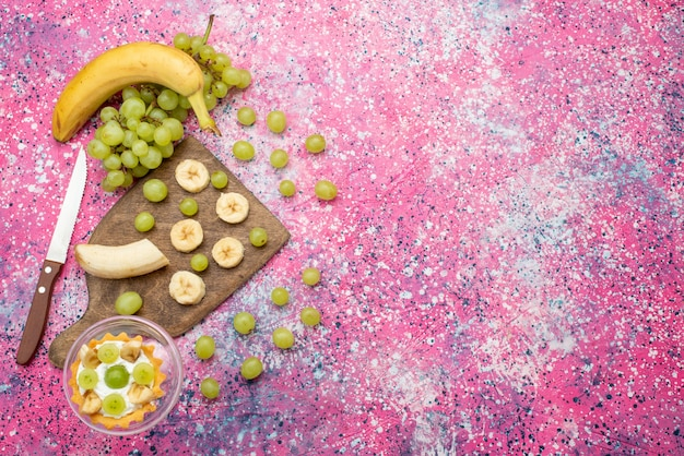 Вид сверху маленький торт со свежим виноградом и бананами на ярко-фиолетовой поверхности фруктовый торт свежего мягкого цвета