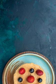 짙은 파란색 책상 위에 신선한 딸기를 올려놓은 작은 케이크