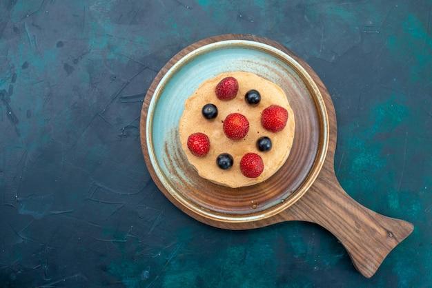 紺色の机の上に新鮮なイチゴが乗った上面図の小さなケーキ