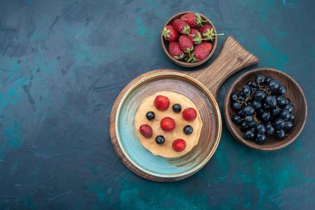 짙은 파란색 책상 위에 신선한 딸기가 있는 작은 케이크