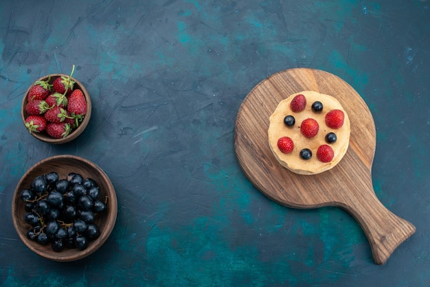 紺色の表面に新鮮なイチゴと上面図の小さなケーキ