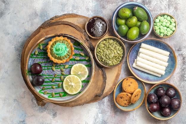 Вид сверху маленький торт с фруктами и конфетами