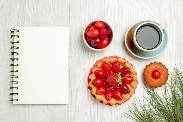 白い机の上にフルーツとお茶のトップビューの小さなケーキ