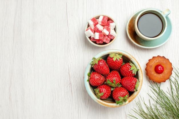 흰색 책상에 과일과 차 한잔과 함께 상위 뷰 작은 케이크