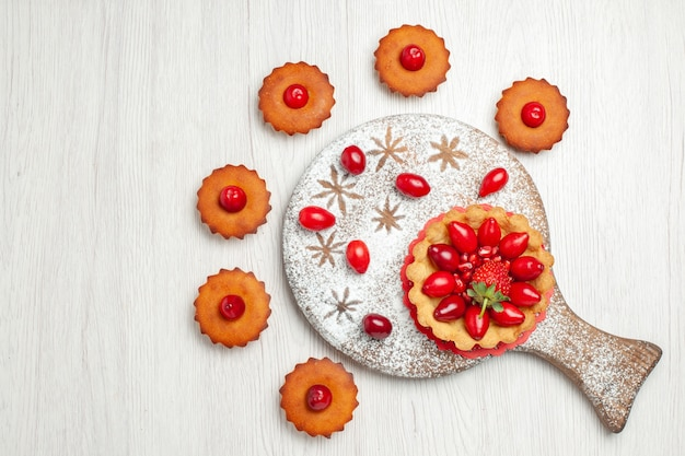 Vista dall'alto piccola torta con frutta e torte sulla scrivania bianca